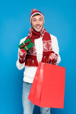 Photo for Happy young adult man in warm clothing holding small gift box and red paper bag isolated on blue - Royalty Free Image