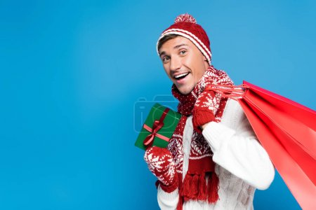 Photo for Excited young adult man with red paper bags behind back, holding small wrapped present isolated on blue - Royalty Free Image