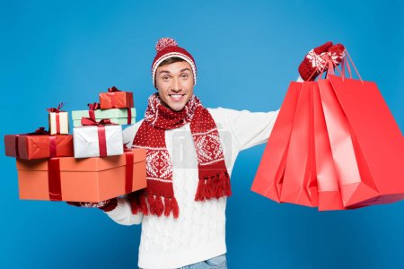 Photo for Front view of happy man in warm clothing holding bunch of gift boxes and red paper bags isolated on blue - Royalty Free Image