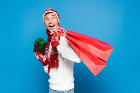 Photo for Excited young adult man with paper bags behind back, holding small gift box isolated on blue - Royalty Free Image