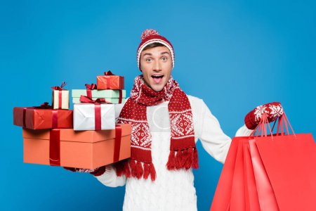 Photo for Front view of surprised man in warm clothing holding bunch of gift boxes and red paper bags isolated on blue - Royalty Free Image