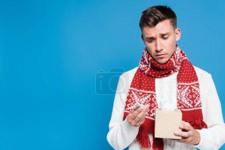 Kranker und verärgerter junger erwachsener Mann blickt auf Thermometer und hält Schachtel mit Taschentüchern auf blauem Grund
