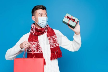 Photo for Young adult man wearing medical mask, holding small gift box and red paper bag, while looking away isolated on blue - Royalty Free Image