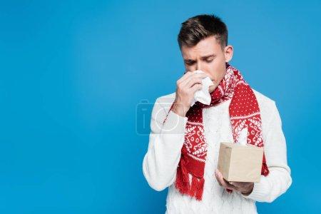 Photo pour Jeune homme adulte en éternuement écharpe rouge, tout en tenant le tissu près du nez isolé sur bleu - image libre de droit
