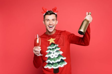 Cheerful man in christmas sweater and headband holding bottle and glass of champagne on red background