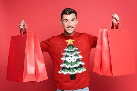 Photo pour Homme souriant en pull avec pin tenant des sacs à provisions et regardant la caméra sur fond rouge - image libre de droit
