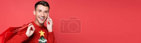 Photo for Young man in christmas sweater smiling while talking on smartphone and holding shopping bags isolated on red, banner - Royalty Free Image