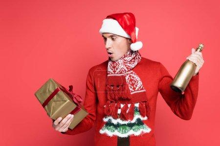 Homme excité en santa chapeau tenant bouteille de champagne et boîte cadeau sur fond rouge