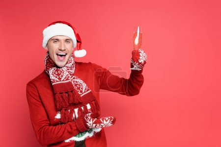Photo for Cheerful man in santa hat and mittens pointing with hand at glass of champagne on red background - Royalty Free Image