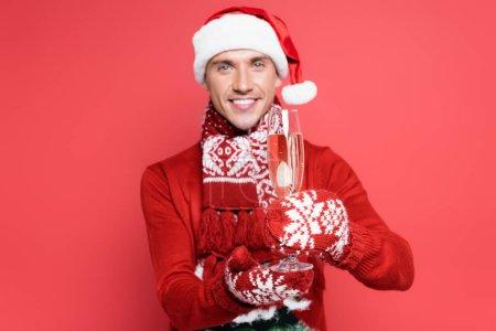 Foto de Copa de champán en manos del hombre en sombrero de santa y mitones sobre fondo rojo y borroso - Imagen libre de derechos