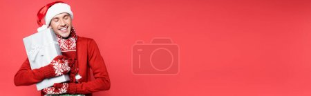 Photo for Smiling man in mittens and santa hat holding gift box isolated on red, banner - Royalty Free Image