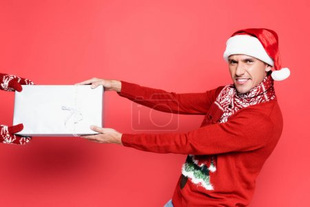 Smiling man in santa hat pulling present on red background