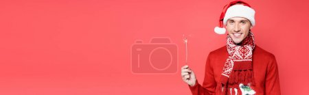 Photo for Young man in santa hat smiling at camera while holding sparkler isolated on red, banner - Royalty Free Image