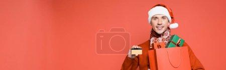 Photo pour Homme souriant au chapeau de Père Noël tenant carte de crédit et sac à provisions avec des boîtes-cadeaux isolées sur rouge, bannière - image libre de droit