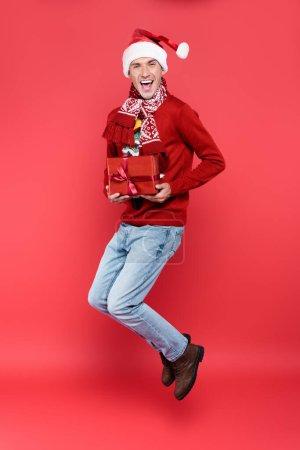 Photo pour Homme gai dans santa chapeau tenant boîte cadeau tout en sautant sur fond rouge - image libre de droit