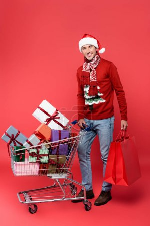 Photo for Smiling man in santa hat holding shopping bags near cart with gift boxes on red background - Royalty Free Image