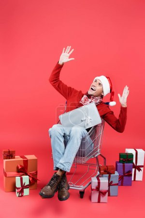 Photo for Cheerful man in scarf and santa hat sitting in shopping cart near gifts on red background - Royalty Free Image