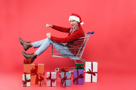 Photo pour Vue latérale du jeune homme en santa chapeau regardant la caméra tout en étant assis dans le panier près de cadeaux sur fond rouge - image libre de droit