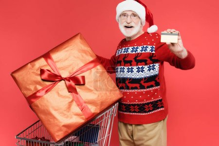Photo for Smiling elderly man in santa hat holding credit card near gifts in shopping cart on red background - Royalty Free Image