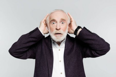 Surprised elderly man in jacket and shirt touching head isolated on grey