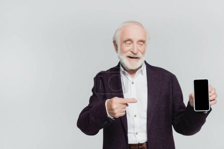 Smiling senior man pointing with finger at smartphone with blank screen isolated on grey