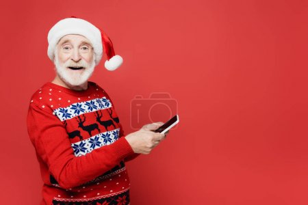 Photo for Smiling elderly man in santa hat holding smartphone isolated on red - Royalty Free Image
