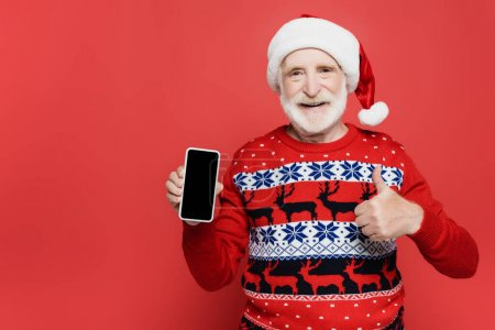 Photo for Smiling elderly man in santa hat showing like and holding smartphone with blank screen on red background - Royalty Free Image