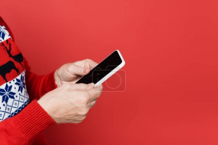 Cropped view of senior man in knitted sweater holding smartphone with blank screen isolated on red