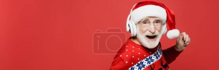 Cheerful senior man in santa hat and headphones dancing isolated on red, banner