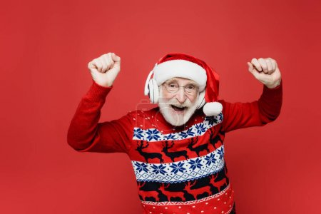 Photo for Senior man in santa hat and sweater dancing while using headphones isolated on red - Royalty Free Image