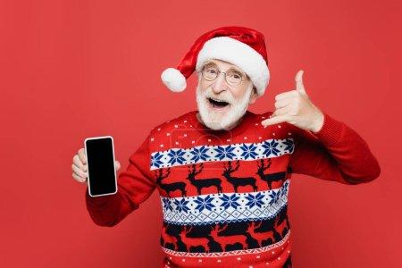 Photo pour Homme âgé joyeux en chapeau et pull Santa montrant smartphone avec écran vide et geste isolé sur rouge - image libre de droit