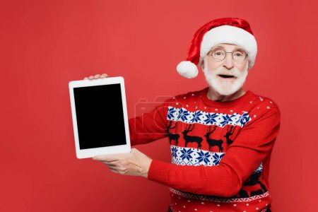 Photo for Senior man in santa hat holding digital tablet with blank screen isolated on red - Royalty Free Image