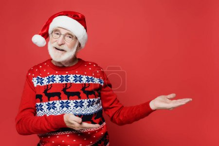 Photo for Smiling elderly man in sweater and santa hat pointing with hands on red background - Royalty Free Image