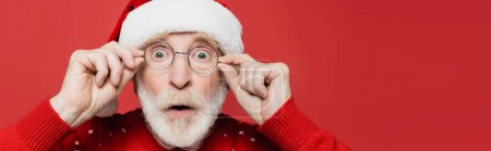 Photo for Surprised senior man in santa hat and eyeglasses looking at camera isolated on red, banner - Royalty Free Image