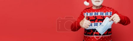 Cropped view of man in santa hat showing like and holding medical mask on blurred background isolated on red, banner