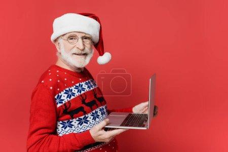Smiling elderly man in santa hat holding laptop on red background