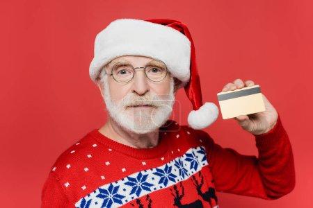 Photo pour Homme âgé en pull et chapeau santa montrant carte de crédit isolé sur rouge - image libre de droit