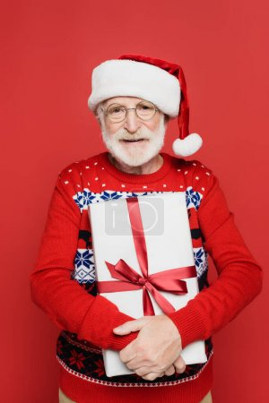 Smiling senior man in santa hat and knitted sweater holding present with ribbon isolated on red