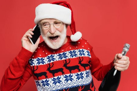 Cheerful senior man in santa hat talking on smartphone while holding bottle of champagne isolated on red