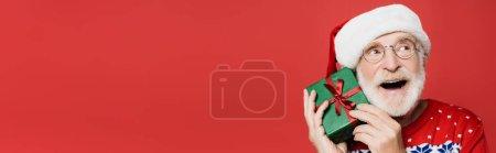 Homme âgé rêveur dans des lunettes et chapeau santa tenant boîte cadeau isolé sur rouge, bannière