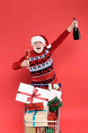 Photo for Smiling senior man in santa hat holding glass and bottle of champagne near presents in shopping cart isolated on red - Royalty Free Image