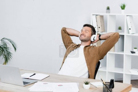 Smiling businessman with closed eyes relaxing while sitting at workplace with laptop