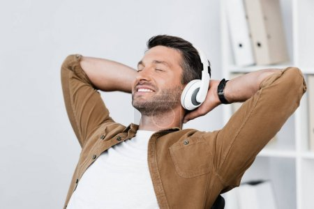 Smiling businessman in headphones relaxing while listening to music on blurred background