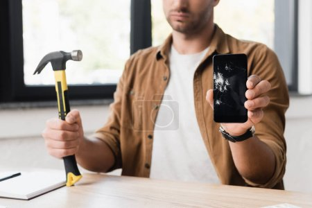 Cropped view of businessman with hammer showing damaged smartphone while sitting at workplace on blurred background
