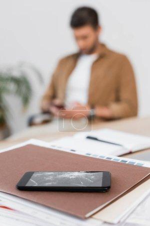Photo pour Smartphone écrasé sur pile de papiers sur la table avec un homme d'affaires flou en arrière-plan - image libre de droit