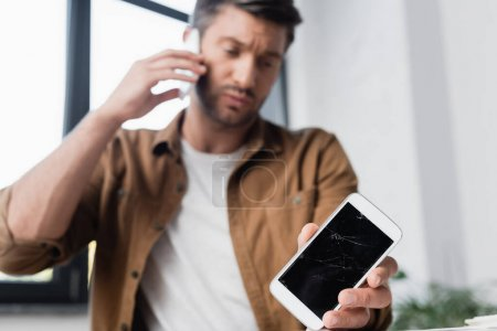 Photo for Smashed smartphone in hand of businessman talking on mobile phone with blurred window on background - Royalty Free Image