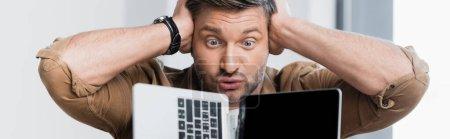Photo pour Homme d'affaires fou avec les mains près de la tête regardant ordinateur portable cassé sur fond flou, bannière - image libre de droit