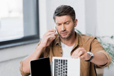 Photo pour Homme d'affaires sceptique regardant ordinateur portable cassé tout en parlant sur un téléphone mobile sur fond flou - image libre de droit
