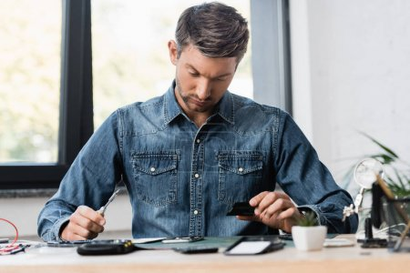 Photo for Focused repairman with screwdriver nad part of disassembled mobile phone sitting at workplace on blurred foreground - Royalty Free Image