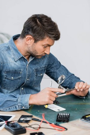 Photo for Repairman with screwdriver looking through magnifier at disassembled part of mobile phone at table on blurred foreground - Royalty Free Image